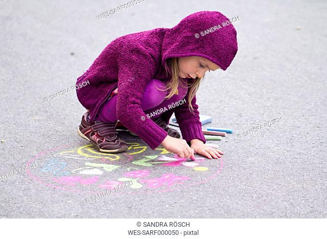 Germany, Girl drawing on street with chalk