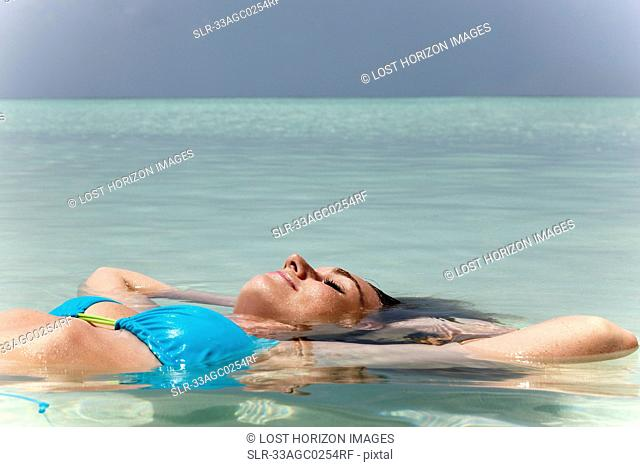 Woman floating in tropical sea