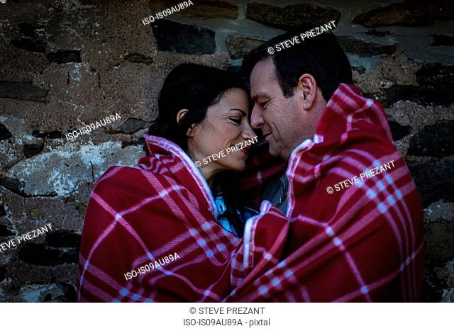 Romantic mature couple face to face wrapped in blanket at night
