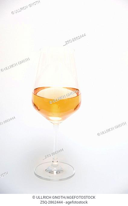 Orange wine (rosé wine) in a stem glass isolated on a white background