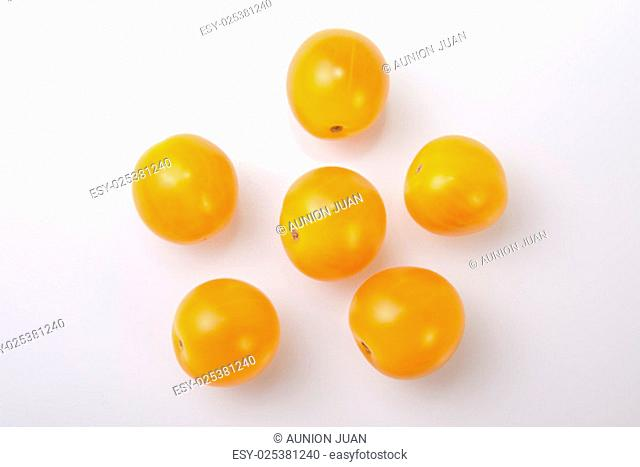 Yellow shiny cherry tomatoes. Isolated over white background