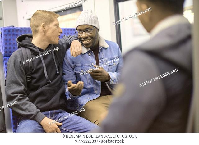 young men sitting in public transport, in Munich, Germany