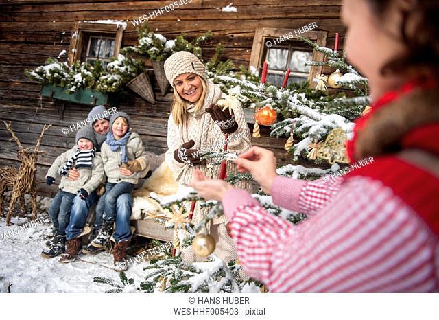Austria, Altenmarkt-Zauchensee, family decorating Christmas tree in front of farmhouse