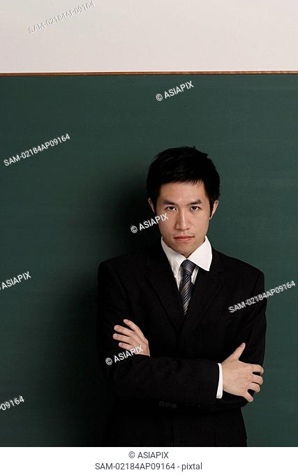 Businessman standing against black wall with arms crossed