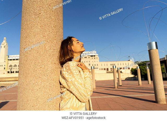 Spain, Barcelona, Montjuic, young woman leaning against a column in sunlight