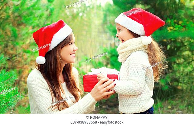 Christmas and family concept - child and mother in santa red hat with box gift