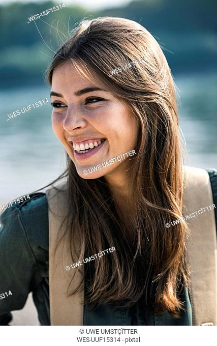 Portrait of happy young woman sitting outdoors
