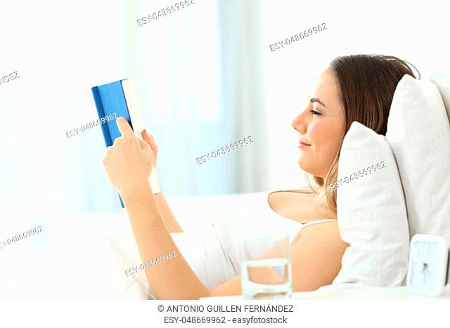 Profile of a satisfied woman reading a paper book on the bed at home