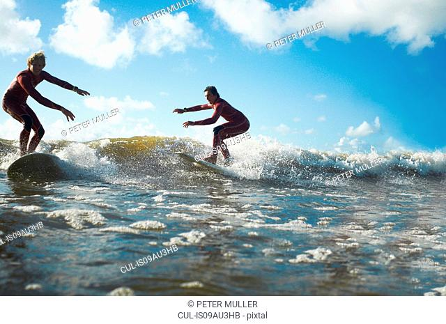 Two surfers riding wave