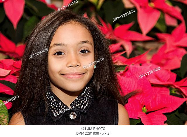 Young girl posing in front of poinsettia plants in a shopping centre; St. Albert, Alberta, Canada