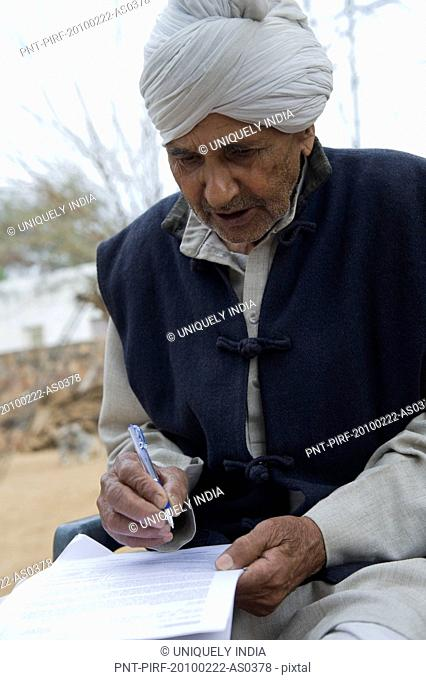 Farmer signing a document, Hasanpur, Haryana, India