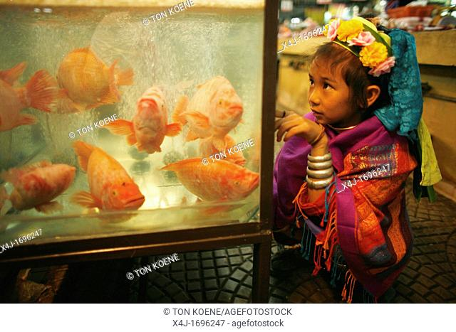 A young Longneck girl looks at fish for sale at a market Approximately 300 Burmese refugees in Thailand are members of the indigenous group known as the...