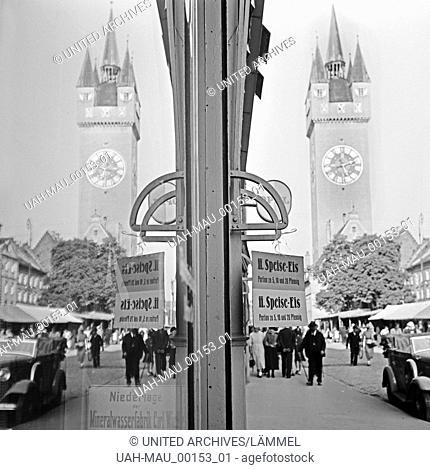 Der Stadturm von Straubing spiegelt sich in der Schaufensterscheibe eines Eisladens, Deutschland 1930er Jahre. Straubing city tower reflecting in a shop window...