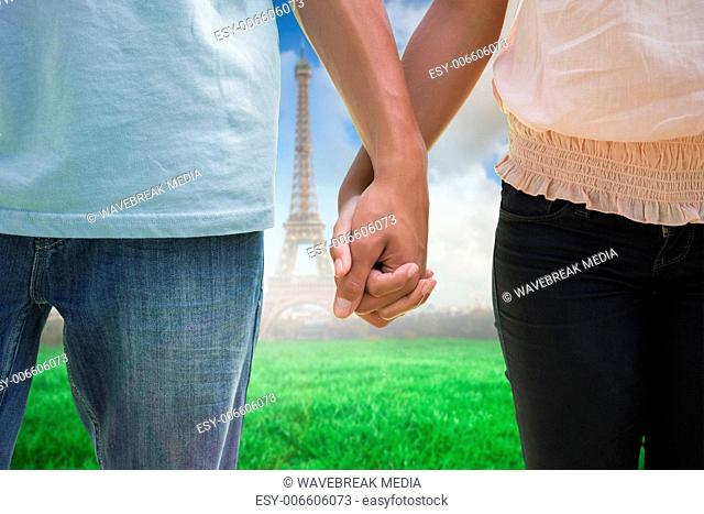 Composite image of young couple holding hands in the park