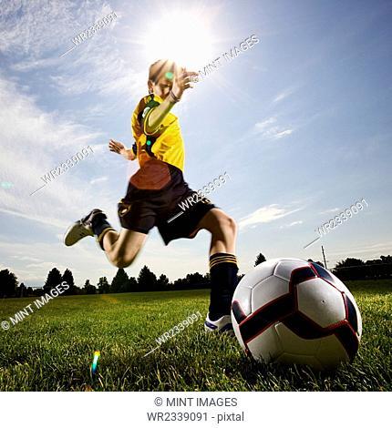 A soccer player, a boy preparing to kick a soccer ball