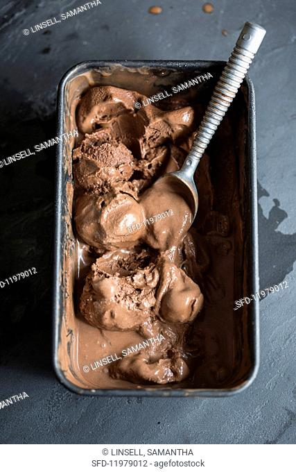 Partially melted chocolate ice cream with an ice cream scoop in a container