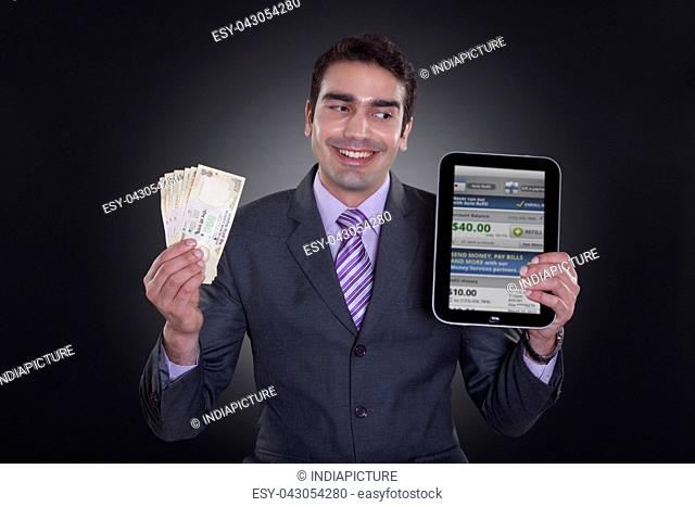 Businessman with currency and digital tablet