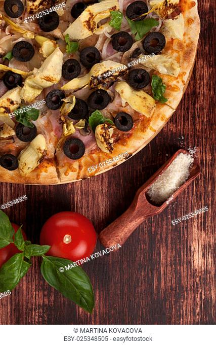 Rustic, country style pizza background. Pizza with black olives, ham and artichokes on wooden background with parmigiano cheese, tomatoes and basil