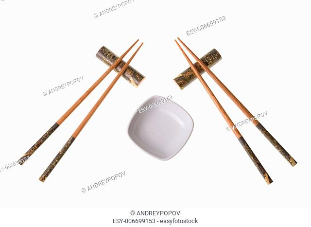 Two pairs of wooden chopsticks and white empty saucer. Sticks are decorated with temple theme ornamentation. Isolated on white
