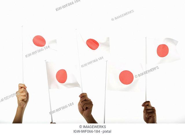 Three people holding Japanese flag, close-up