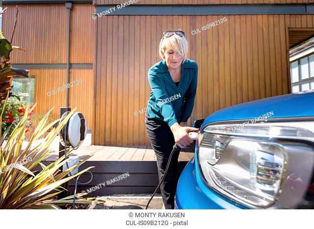 Woman charging electric car from charging point