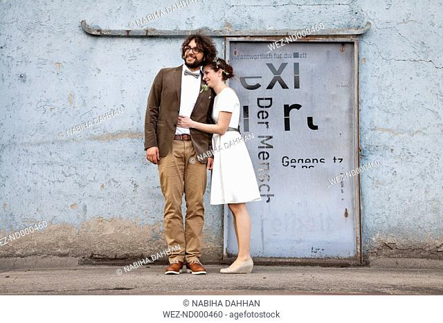 Bridal couple standing in front of an old industrial building