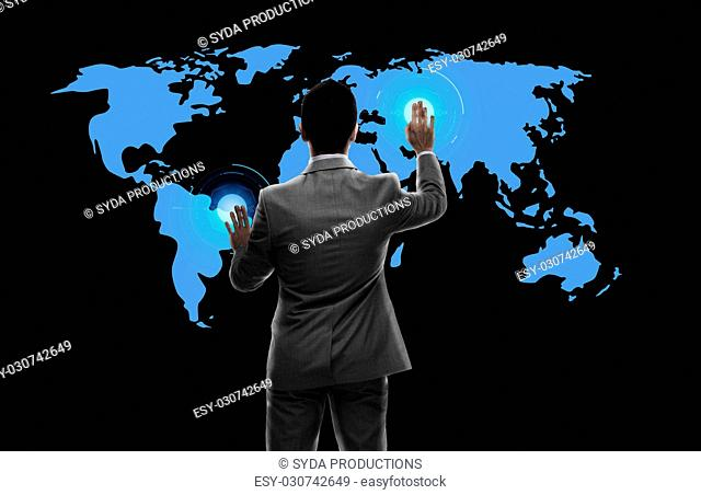 business, people and technology concept - businessman working with virtual world map from back over black background