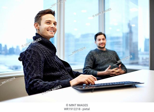 Two men in a office seated at a desk chatting and smiling