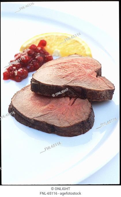 Roast beef, cranberry sauce and slice of orange on plate