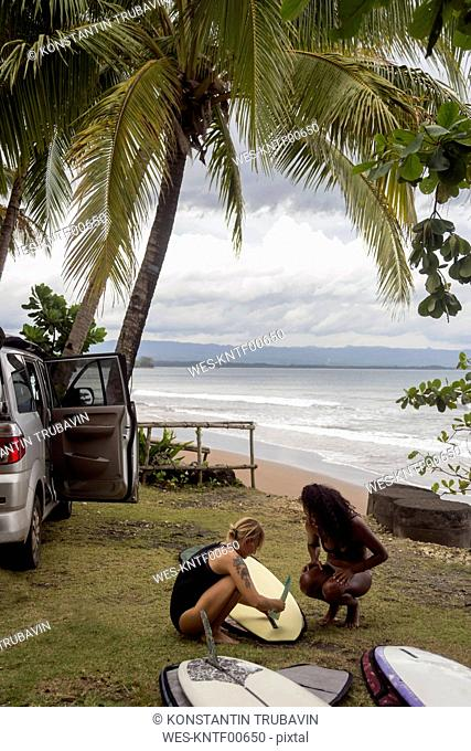 Indonesia, Java, two women preparing surfboard at the coast