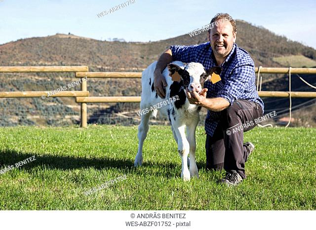 Portrait of smiling farmer with calf on pasture