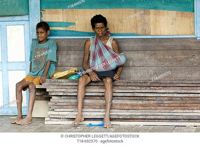 Mother and son sitting on planks of iron wood, Indonesia