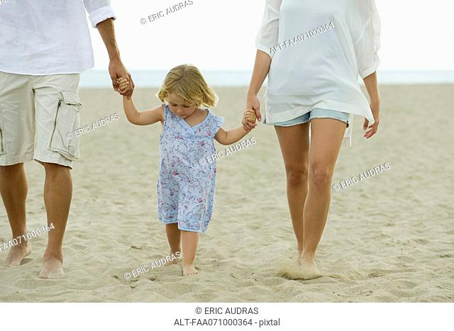 Little girl walking on beach with her parents, cropped