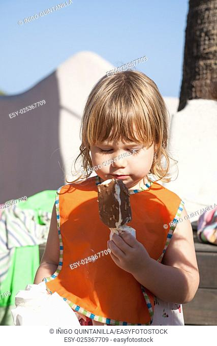 portrait of three years old blonde happy child with orange bib eating chocolate and white popsicle ice cream in exterior