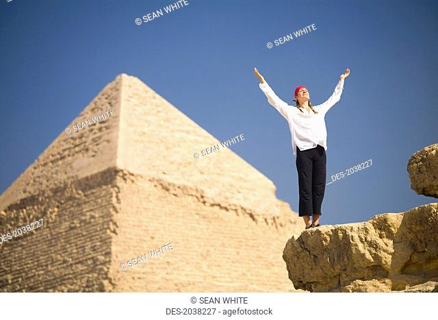 A Woman Tourist Raises Her Arms In Front Of The Pyramids Of Giza Near Cairo, Giza Egypt