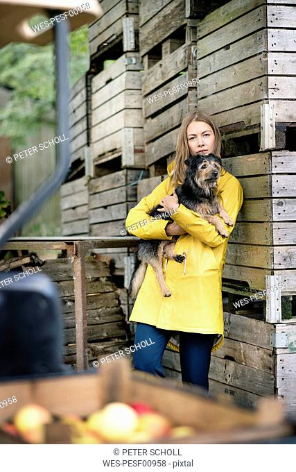 Woman on a farm standing at wooden boxes holding dog