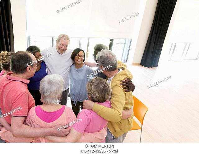Active seniors hugging in circle