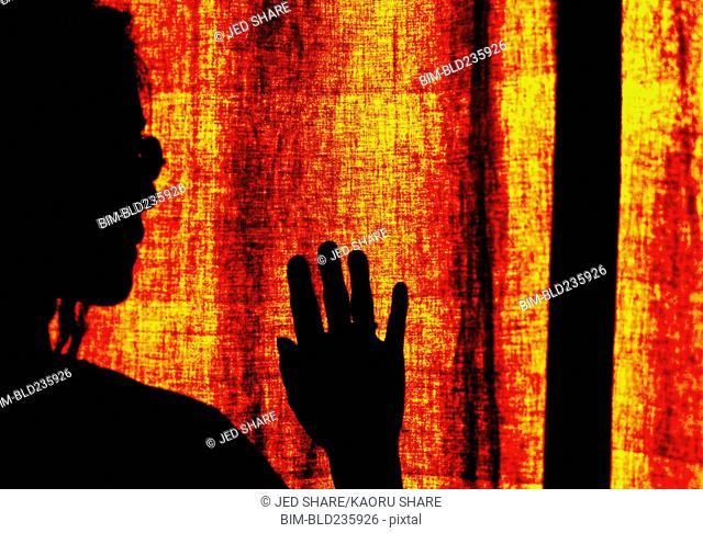 Silhouette of Japanese woman at orange curtain
