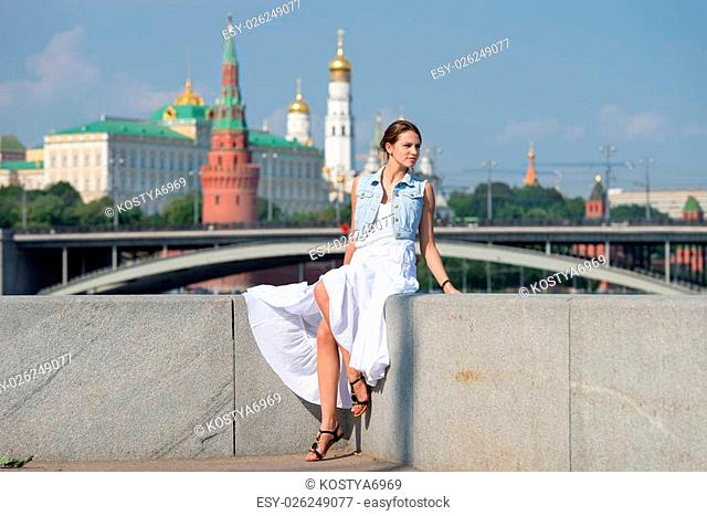 Beautiful girl in white dress sitting on the parapet of the embankment of the river on the background of the Moscow Kremlin