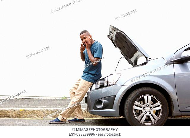 Full length portrait of upset young african man standing in front of a broken car and making a phone call for help