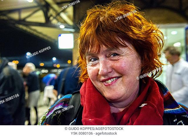 Roosendaal, Netherlands. Portrait of a smiling, Read haired woman, waiting on the railway station's platform for the last train to Brussels. Ever