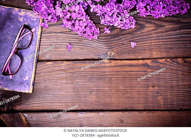 branch of a purple lilac and an old book with glasses on a brown wooden background, an empty space