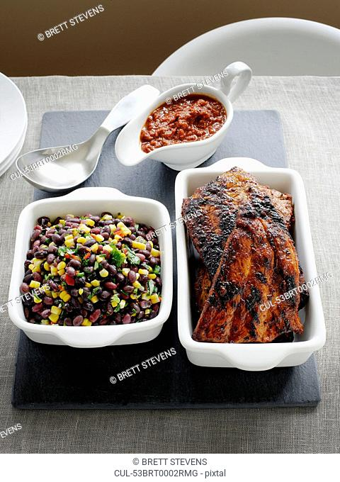 Dishes of pork ribs and black bean salad