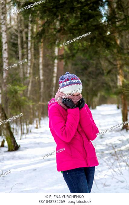 Portrait of a teenage girl in a bright pink winter jacket and knitted hat, which covers her face with a scarf. She stay in the winter snowy forest