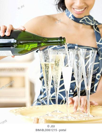 Mixed Race woman pouring champagne