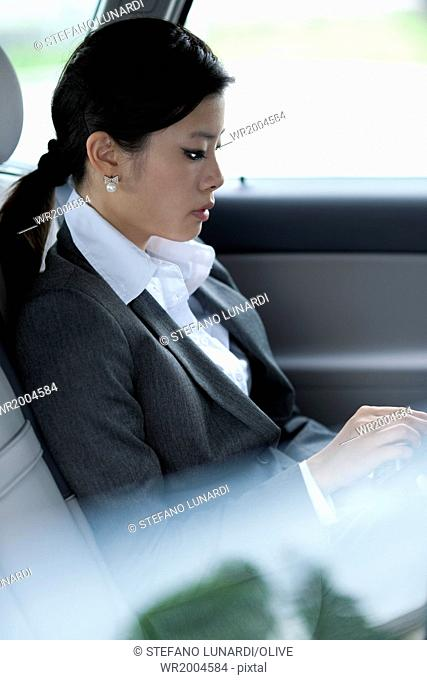 Young chinese business woman inside a car