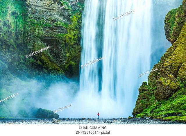 Man standing at base of Skogafoss waterfall; Iceland