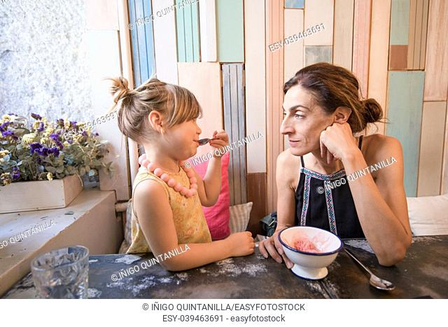 Three years old blonde girl with yellow dress an necklace eating strawberry ice cream with spoon from bowl, looking at woman mother