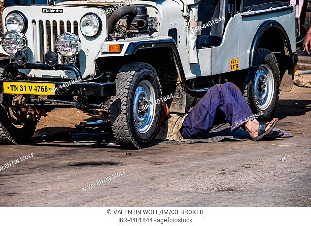 Man laying under Jeep for maintenance, Tamil Nadu, India