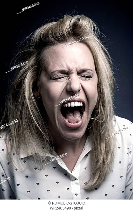 Young woman with blond hair screaming